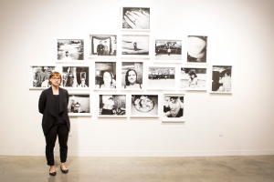 """Ashley Strazzinski stands with her collection of photographs entitled """"Social Objectification"""" at the BFA reception on Nov. 21."""
